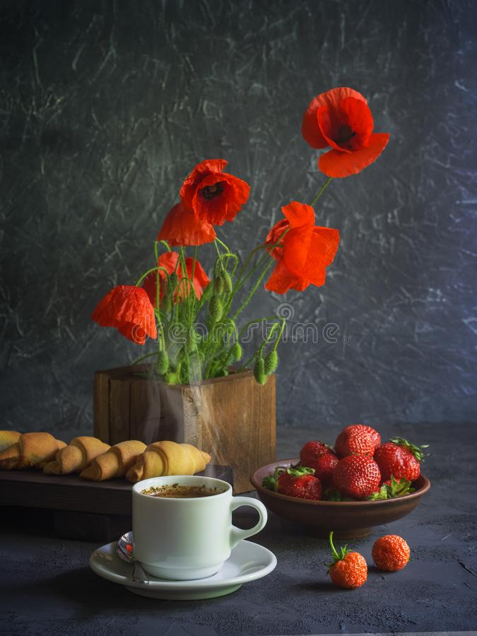 Vintage background with red poppies in a wooden vase, a cup of coffee, strawberries in a plate and croissants on a wooden tray royalty free stock photography