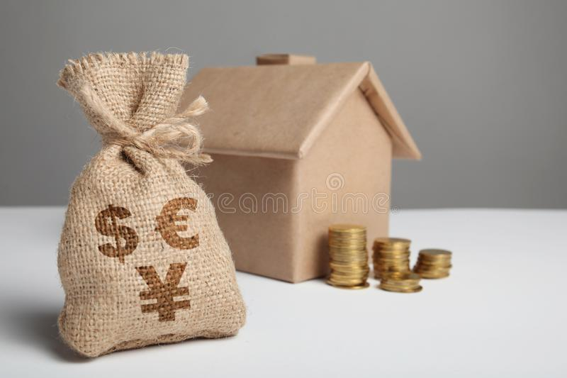 Vintage bag with dollar, euro and yuan sign and yellow coins on the background of the craft figure of the house. Home insurance. And mortgages. Buy real estate stock image