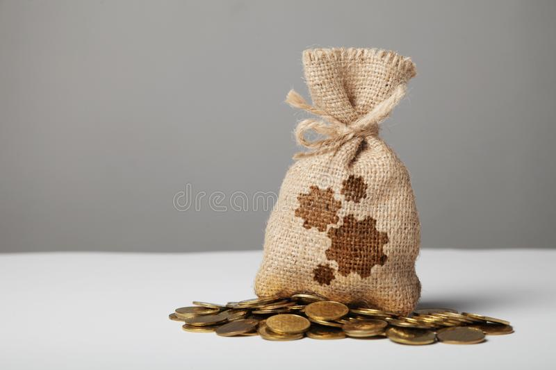 Vintage bag with money on gold coins. Gears symbol, established profitable business stock photography