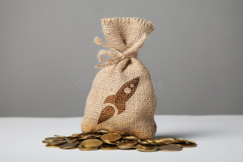 Vintage bag with money on gold coins. Symbol of rocket and growth royalty free stock images