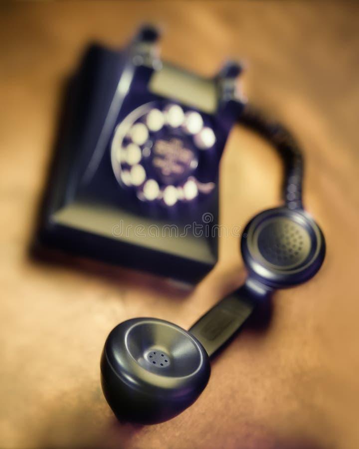 Vintage bakelite dial telephone on rustic metal surface. Selective focus. Old black bakelite dial telephone on rustic metal surface. Selective focus stock images