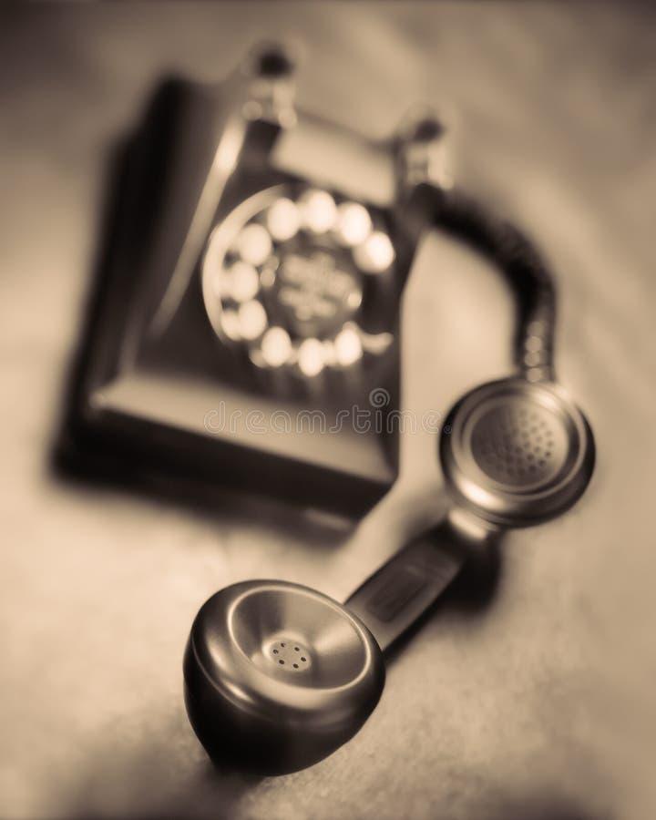 Vintage bakelite dial telephone on rustic metal surface. Selective focus. Old black bakelite dial telephone on rustic metal surface. Selective focus, sepia tone royalty free stock photography