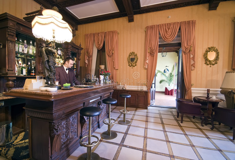 Vintage bar. A vintage bar of a classic hotel, the bartender working royalty free stock photos