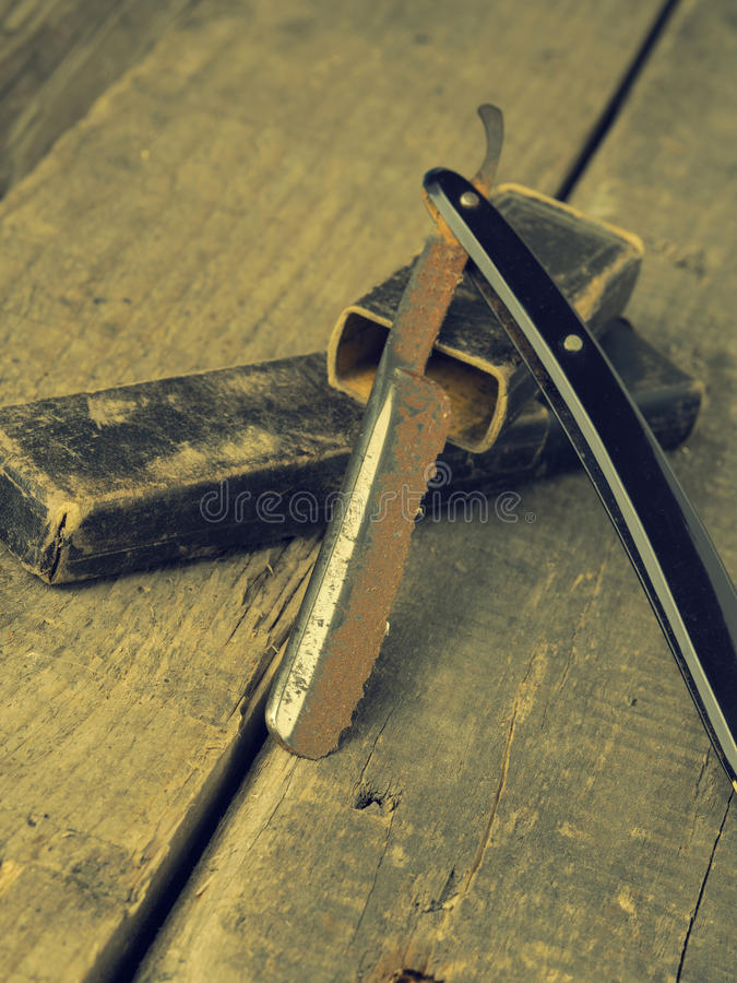 Vintage barber concept with rusty razor. Old and rusty razor on a rustic workbench with space for text or image stock photography