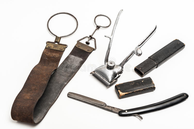 Vintage barber tools. Old and worn rusty razor, razor case, sharpening leather and a metal trimmer on a white background royalty free stock photography