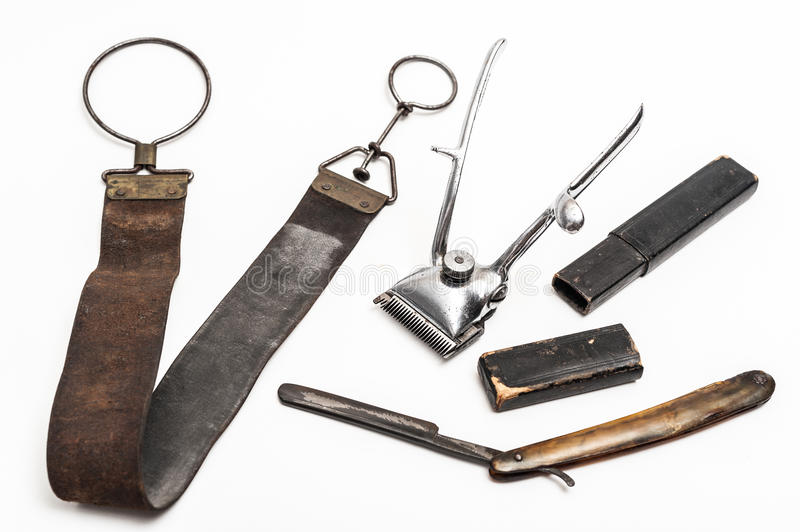 Vintage barber tools. Old and worn rusty razor, razor case, sharpening leather and a metal trimmer on a white background stock photos