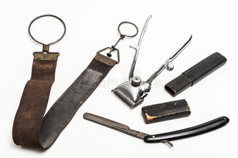 Vintage barber tools. Old and worn rusty razor, razor case, sharpening leather and a metal trimmer on a white background royalty free stock photos