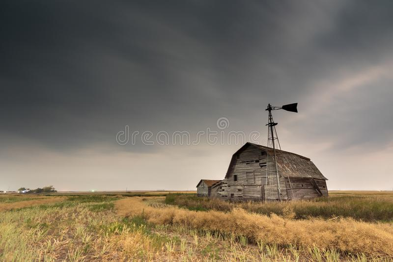 Vintage barn, bins and windmill under ominous dark skies in Saskatchewan, Canada. Vintage barn, bins and windmill in a swathed canola field under ominous dark stock image