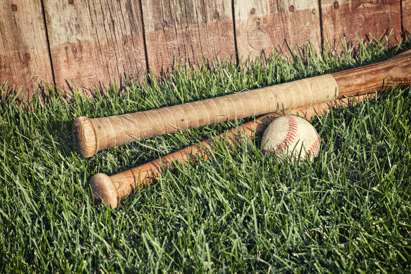 Vintage baseball and bats on grass near old wooden fence royalty free stock images