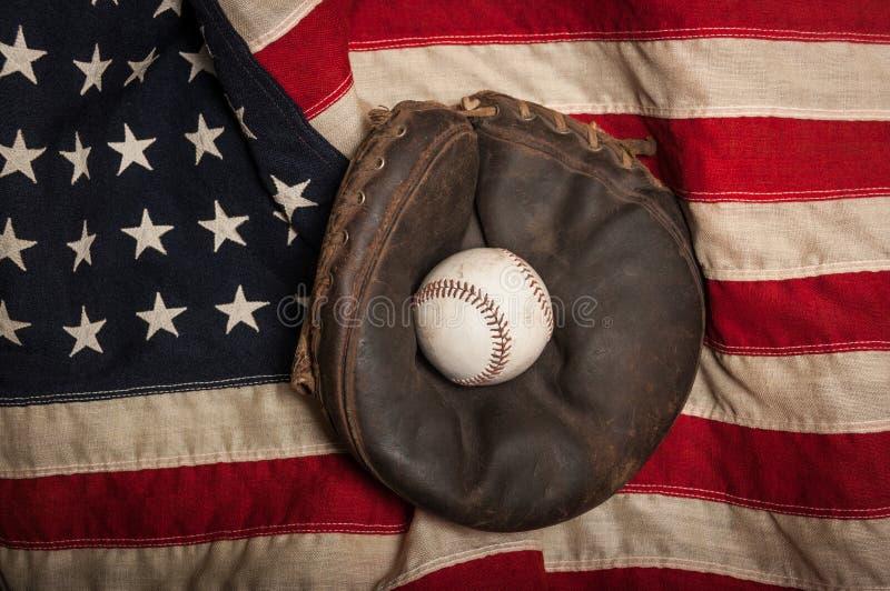 Vintage baseball glove on an American flag. Vintage baseball mitt with a baseball sitting on an American flag royalty free stock image
