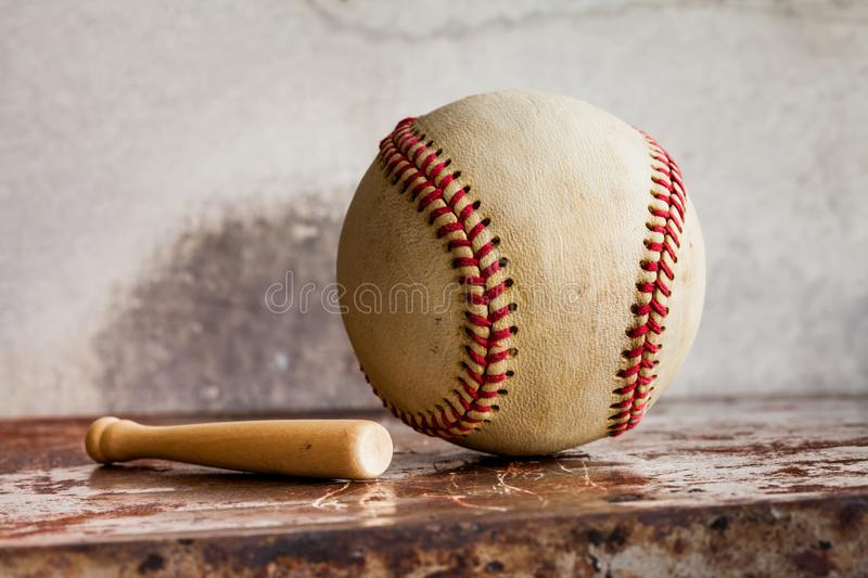 Vintage baseball and small wooden bat. Sport equipment on retro style metal texture background. Macro view ball, shallow stock images