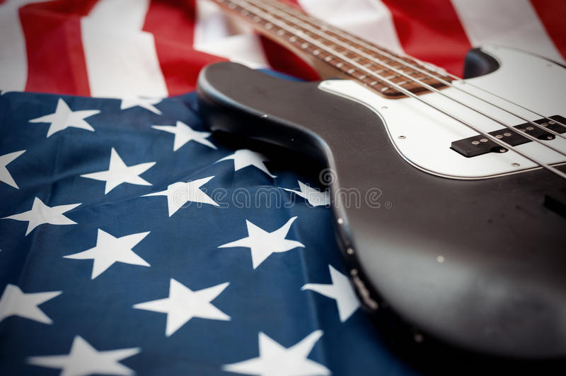 Vintage bass guitar on american flag background. Vintage four strings bass guitar close up on an american flag background stock photo