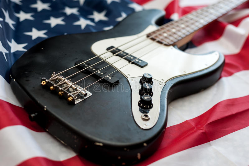 Vintage bass guitar on american flag background. Vintage retro four strings bass guitar close up on an american flag background royalty free stock image