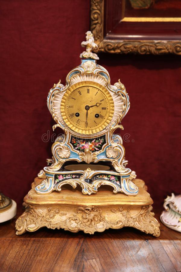 Vintage beautiful clock with porcelain trim on a table. Vintage beautiful clock with porcelain trim on a wooden table stock photos