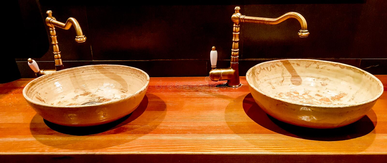 Vintage Beautiful faucet and golden mixer tap on a marble round sink in the bathroom. Interior of an expensive toilet with a. Marble sink royalty free stock images