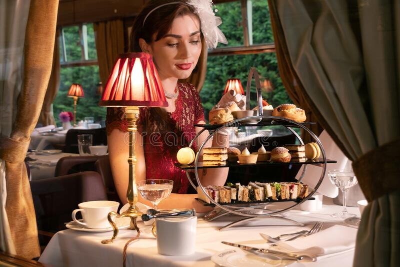 Vintage, beautiful woman in red dress enjoying afternoon tea in train carriage with cakes, sandwiches and tea royalty free stock photo