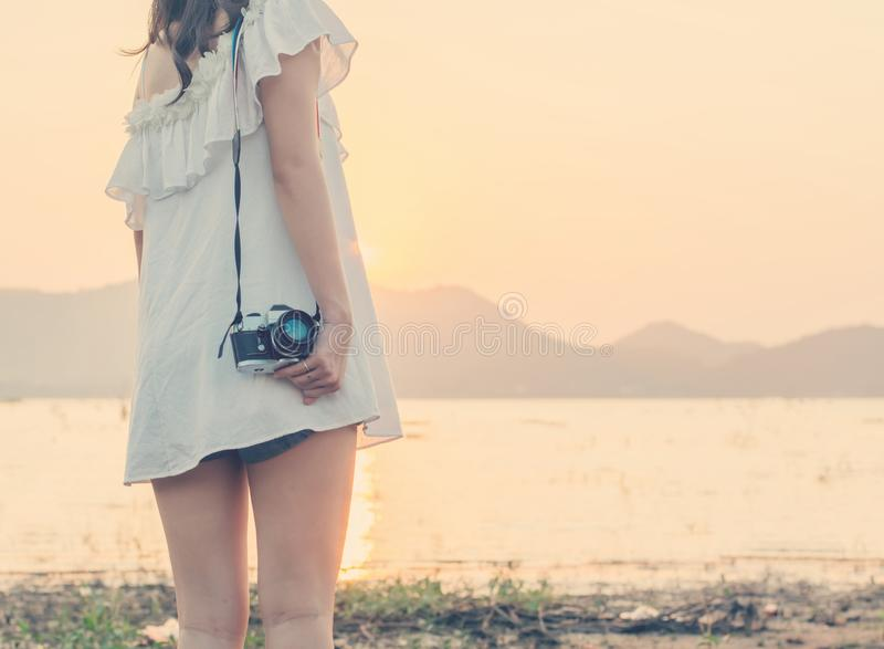 Vintage of beautiful women photography standing hand holding retro camera with sunrise,dream soft style royalty free stock photography