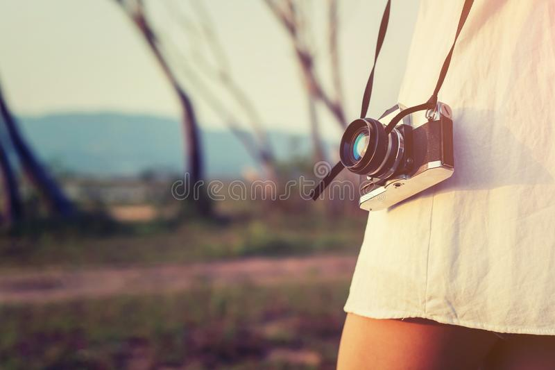 Vintage of beautiful women photography standing hand holding retro camera with sunrise,dream soft style. Background stock photo