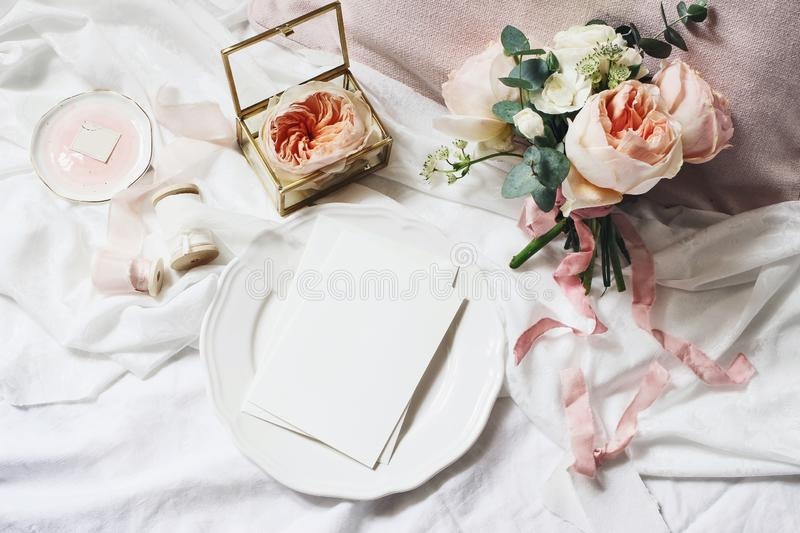 Vintage bedroom still life scene. Wedding, birthday bouquet of pink English roses, Ranunculus flowers and eucalyptus. Greeting card mockup on plate. Ribbons royalty free stock photo