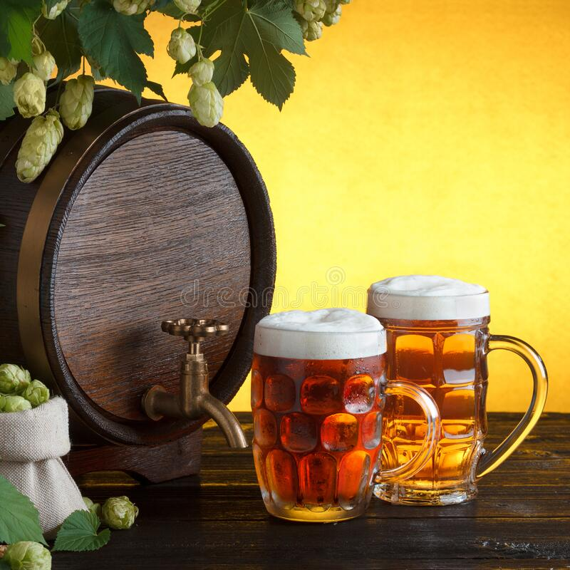 Vintage beer barrel with two beer glasses and frame of fresh hops. On wooden table still life, copy space royalty free stock images
