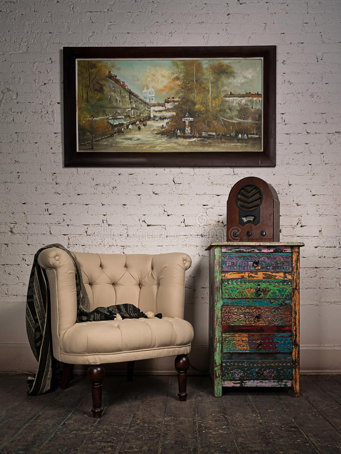 Vintage beige armchair, colorful cupboard, old radio and hanged stock image