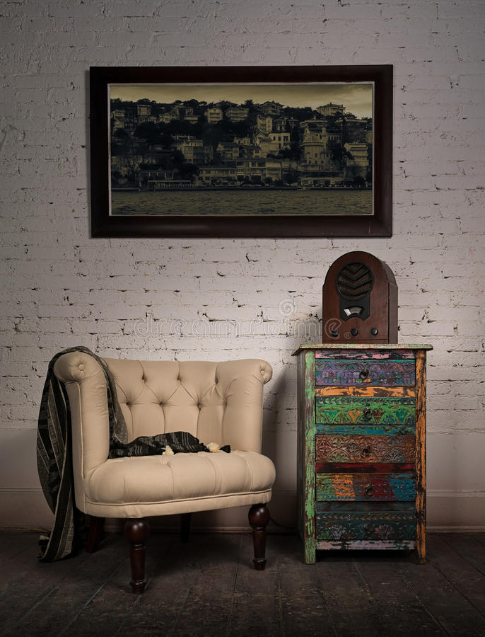 Vintage beige armchair, colorful cupboard, old radio and hanged painting stock photos