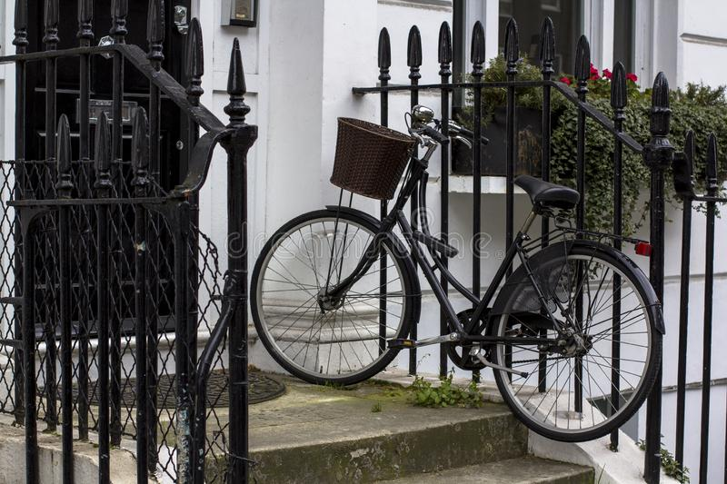 Vintage bicycle with basket on the porch. Entrance Door to residential building in London. Typical door in the English style royalty free stock image