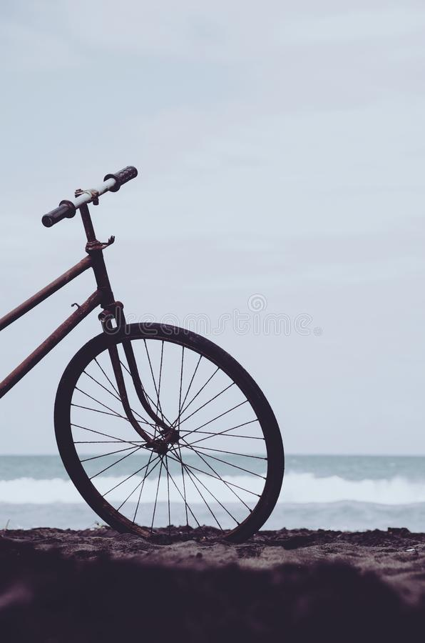 Vintage bicycle on the beach detail, front wheel. Old vintage retro bicycle on the beach. Sea, waves, horizon and sky are visible in the background stock photography