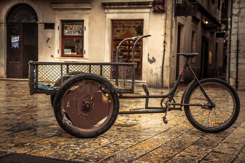 Retro bicycle on vintage europe medieval plaza with stone pavers in overcast day during raining autumn season in old European city royalty free stock photography