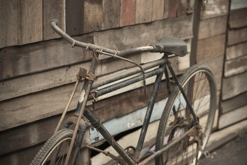 Vintage Bicycle standing near a vintage wood wall.  stock photo
