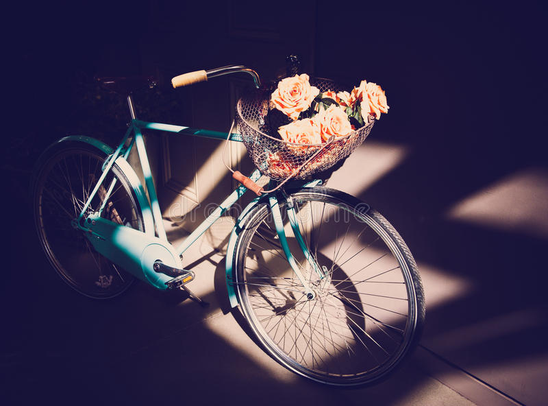 Vintage Blue Bike. Vintage classic bike with bunch of roses in the basket royalty free stock image