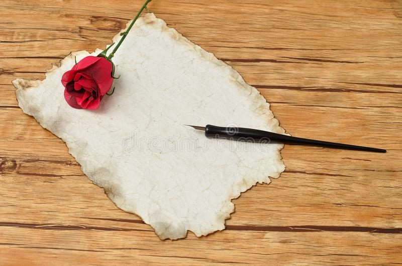 A vintage black fountain pen with old paper and a red rose stock images