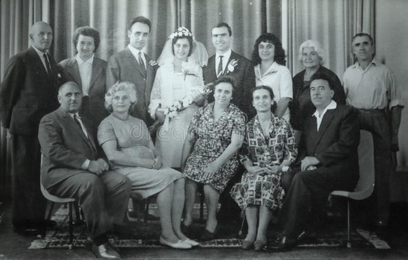 Vintage black and white photo of family wedding, 1950s European. Vintage black and white photo of men and women at family wedding with bride holding flowers royalty free stock photos