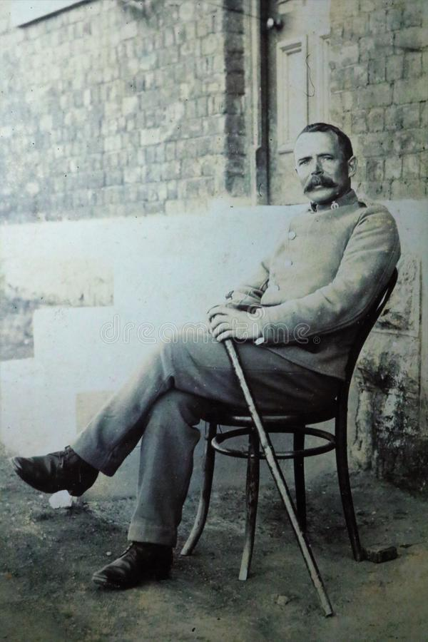 Vintage black and white photo of a man with moustache sat on chair in garden holding walking stick in back yard 1900s. stock image