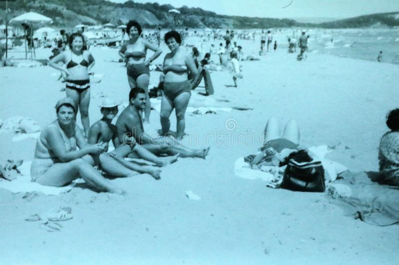Vintage black and white photo of people on a beach enjoying the sun, 1950s European. Vintage black and white photo of a people on a beach enjoying the sun royalty free stock photos