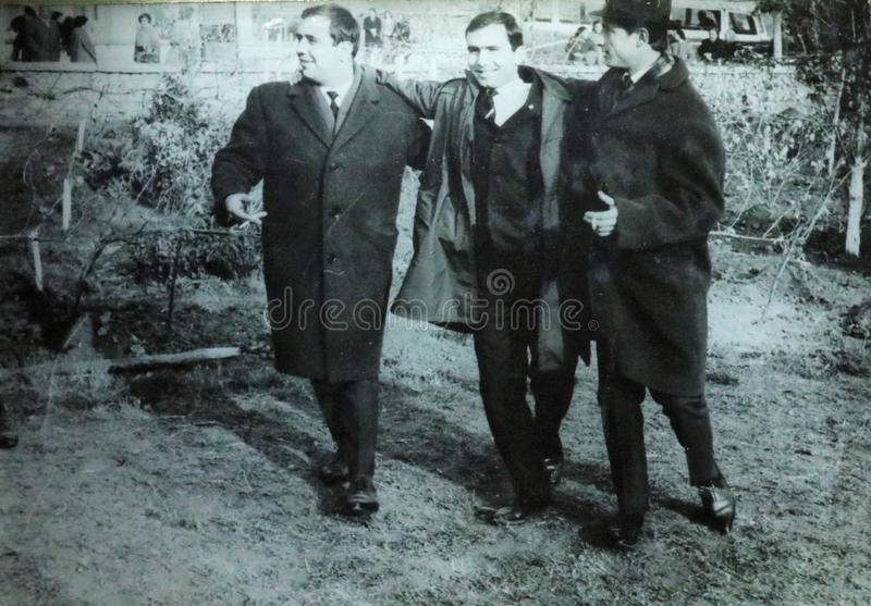 Vintage black and white photo of three men wearing overcoats and smoking, 1950s European. Vintage black and white photo of men wearing overcoats and smoking royalty free stock photography