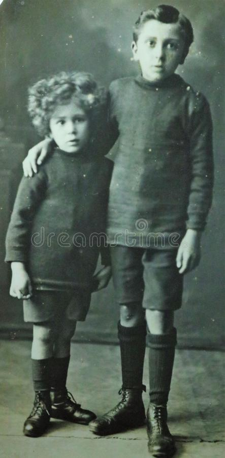 Vintage black and white photo of two young boys wearing shorts and boots, possibly brothers 1900s. royalty free stock photo