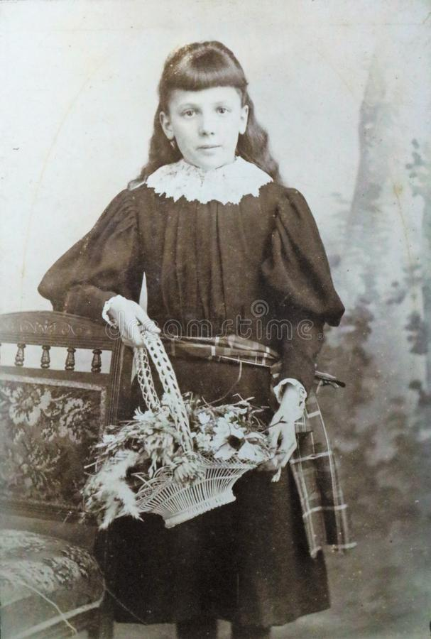 Vintage black and white photo of a young Victorian girl holding a basket of flowers 1880s - 1900s. royalty free stock images