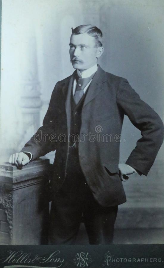 Vintage black and white photo of a young Victorian man with moustache wearing smart suit and big collar shirt 1880s - 1900s. royalty free stock photos