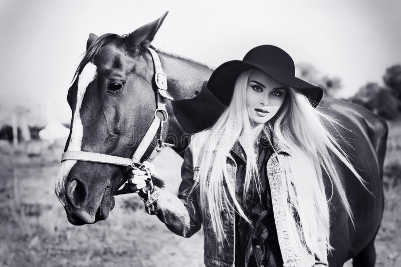 Vintage black and white portrait of a young beautiful caucasian girl holding a horse royalty free stock photo