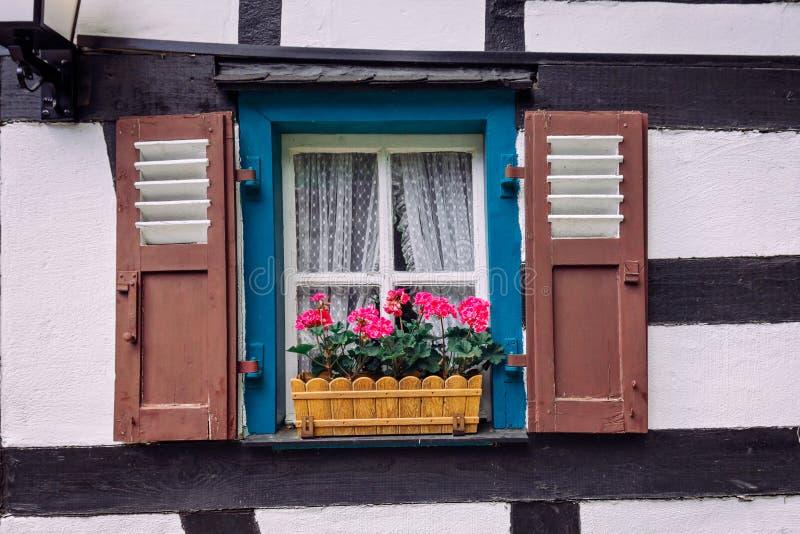 Vintage-blaues Fenster an der weißen Wand mit einem Korb aus rosa Blumen stockbild