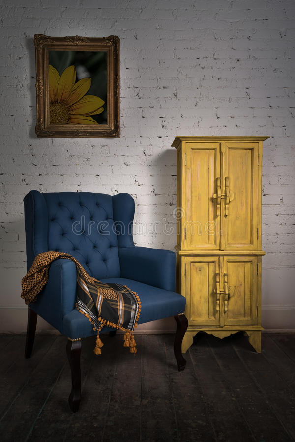 Vintage blue armchair, yellow cupboard and framed painting stock images