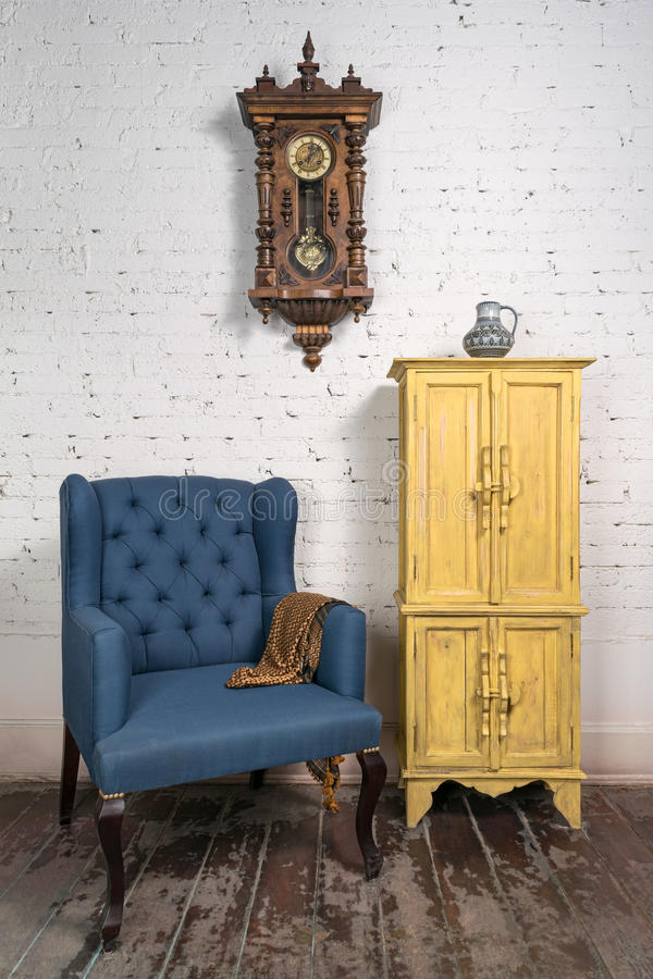 Vintage blue armchair, yellow cupboard, pendulum clock and orange scarf royalty free stock images