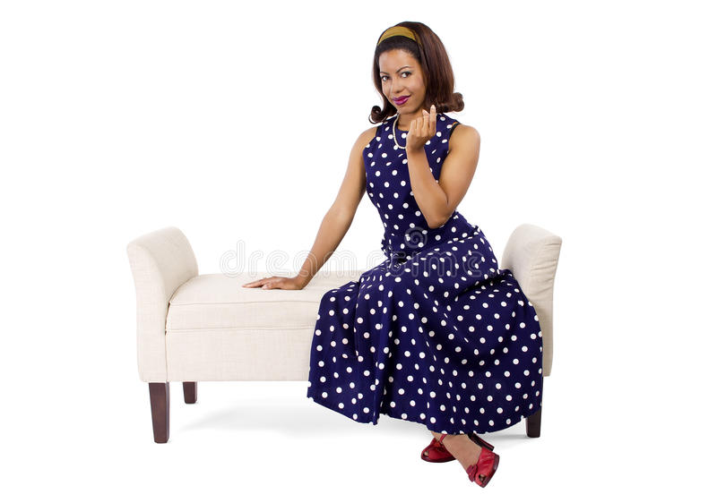 Vintage Blue Poka Dot Dress. Woman wearing a blue polka dot dress on a traditional chaise furniture. The model is isolated on a white background royalty free stock photo