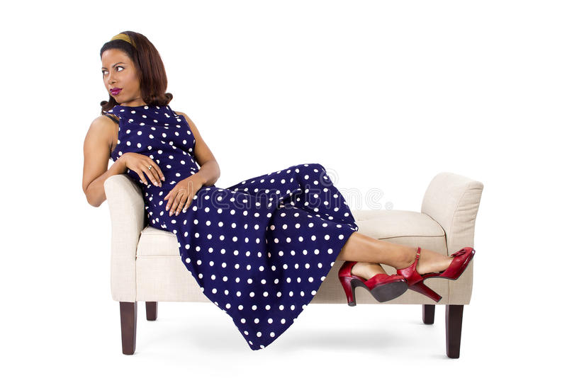 Vintage Blue Poka Dot Dress. Woman wearing a blue polka dot dress on a traditional chaise furniture. The model is isolated on a white background stock images