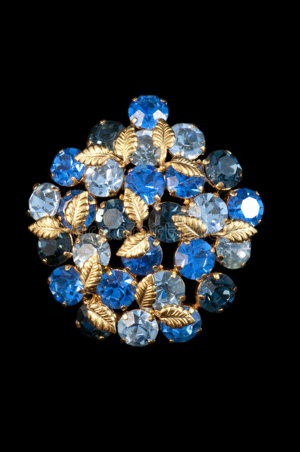 Vintage blue rhinestone brooch. Beautiful blue vintage rhinestone brooch with small gold leaves isolated on a black background stock photo