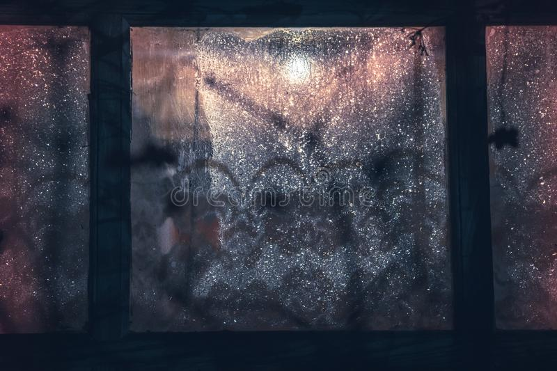Vintage blue toned frozen window as winter retro background stock image