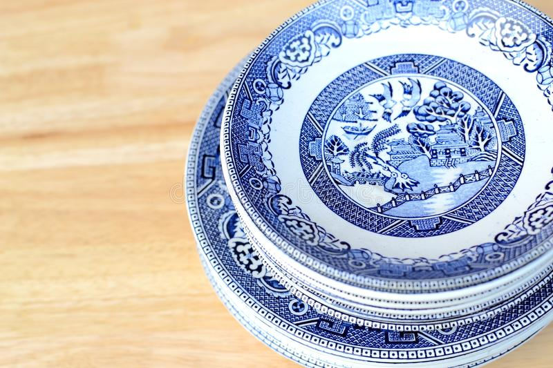 Vintage blue willow pattern china plates. On a table stock photos