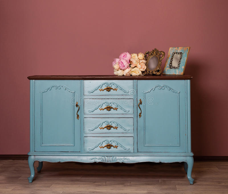 Vintage blue wooden dresser, tender bouquet and two frames. stock images