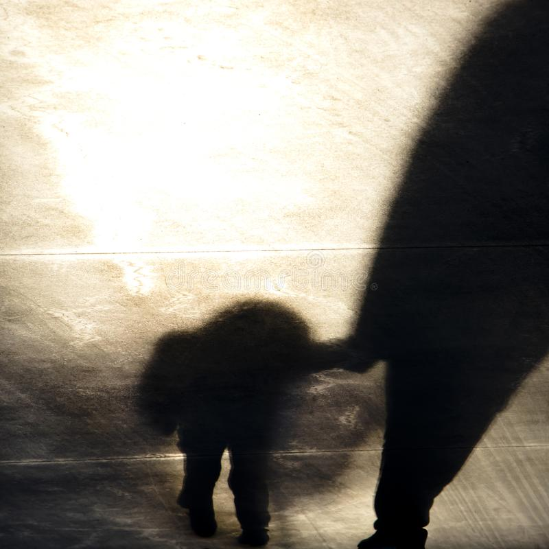 Vintage blurry shadow of a boy and an adult walking stock image